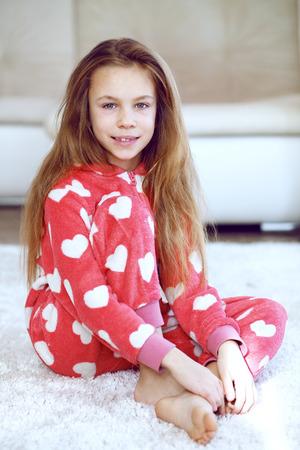 自宅のカーペットの上に座って柔らかい暖かいパジャマの子供の肖像画 写真素材