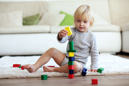 assiduous: Toddler playing with wooden blocks at home Stock Photo
