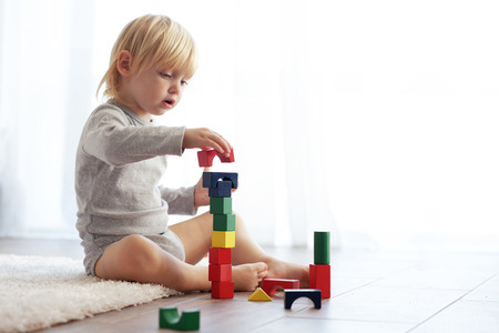 2 years old: Toddler playing with wooden blocks at home Stock Photo