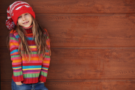 little model: Cute little girl wearing knit winter clothes posing over wooden background Stock Photo