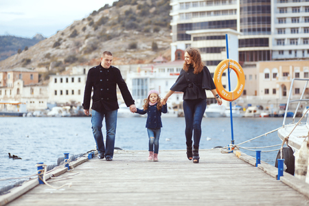 Portrait of happy young family walking with their child on berth near sea in the city, still life photo photo