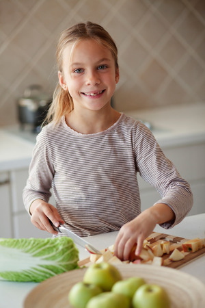 7 years old: Portrait of a 7 years old girl cutting vegetables in kitchen at home
