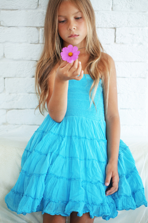 beautiful preteen girl: Kid girl dressed in blue dress holding a flower
