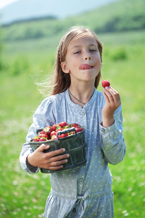 Child eating strawberries in a spring floral field photo