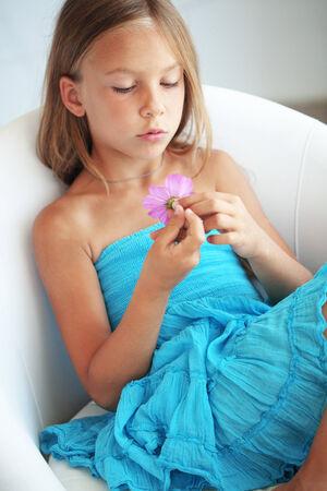 Kid girl dressed in blue dress holding a flower
