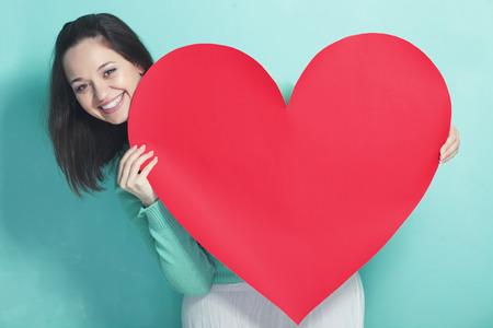 ragazza innamorata: Donna che tiene grande cuore rosso su sfondo blu aqua