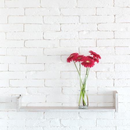 Decoratieve plank op witte bakstenen muur met bloemen in de vaas op het Stockfoto