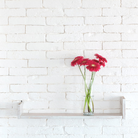 red gerber daisy: Decorative shelf on white brick wall with flowers in vase on it