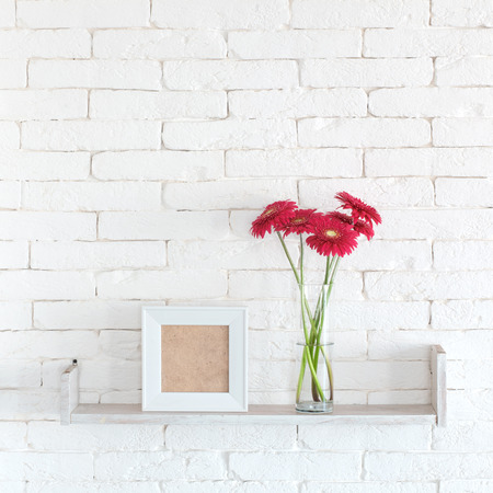 glass brick: Decorative shelf on white brick wall with flowers in vase on it