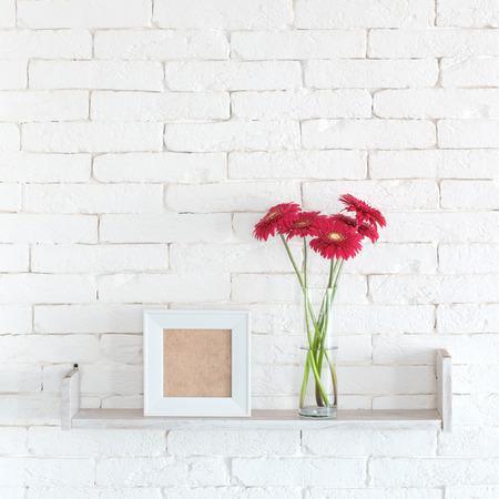 paredes de ladrillos: Estante decorativo en la pared de ladrillo blanco con flores en el florero sobre el mismo