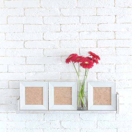 white shelf: Decorative shelf on white brick wall with flowers in vase on it