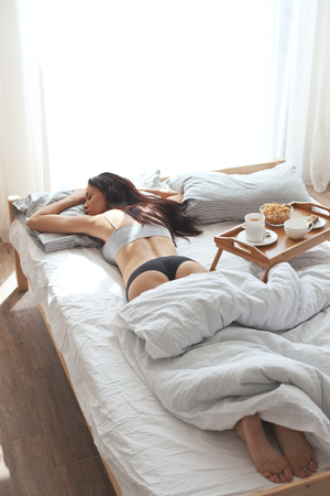 30 years old woman: Portrait of 30 years old woman resting in bed with breakfast on a wooden tray at home in morning, still life photo Stock Photo