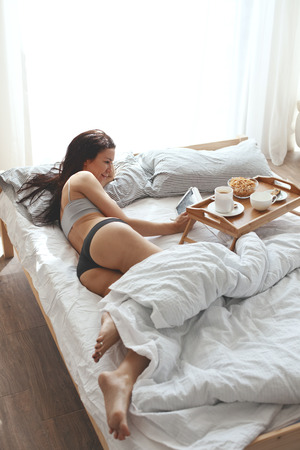 Portrait of 30 years old woman resting in bed with breakfast on a wooden tray at home in morning, still life photo photo