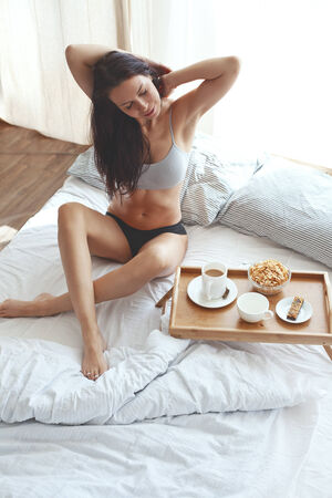 30 years old woman: Portrait of 30 years old woman resting in bed with breakfast on a wooden tray at home in morning, still life photo, top view point