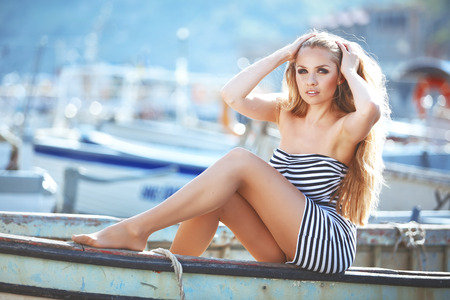 Beautiful sexy model posing on vintage boat at summer beach photo
