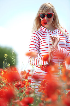 Teenage girl walking in spring flower filed photo