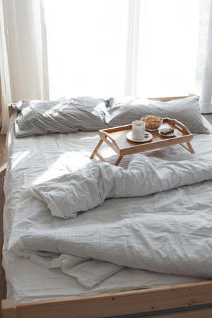 Wooden tray with coffee and breakfast on the bed photo