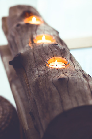 Handmade rustic wooden candlestick on a coffee table in a living room