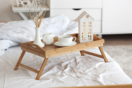 Wooden tray with coffee and interior decor on the bed with white linen Imagens