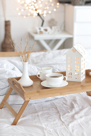 Wooden tray with coffee and interior decor on the bed with white linen Stock Photo
