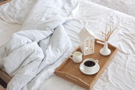 흰색 리넨 침대에 커피와 실내 장식 나무 트레이 스톡 콘텐츠