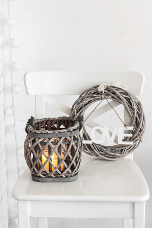 Rustic wreath and lantern on a white shabby chic chair near the wall photo