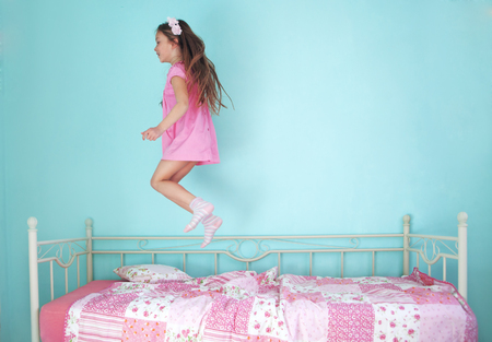 8 years old girl jumping on the bed at home Stock Photo