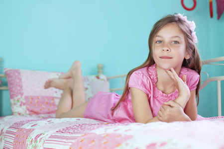 Portrait of 7 years old school girl resting on pink bed in her nursery at home photo