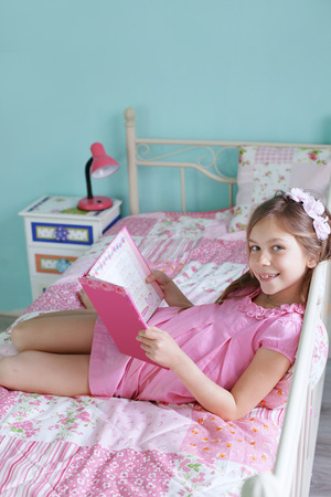 Portrait of 7 years old school girl reading a book on pink bed in her nursery at home photo