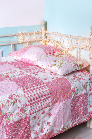 Photo of girls bed with pattern bedding on it photo