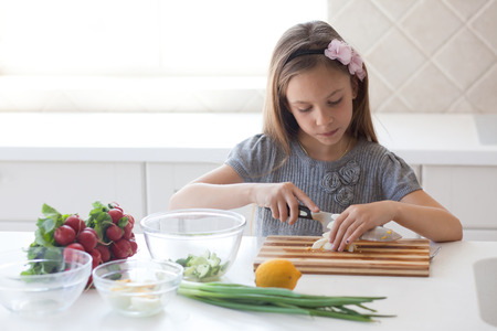 7 - 8 years old girl cooking in the white modern kitchen Stock Photo - 27342724