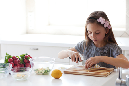 7 8 years: 7 - 8 years old girl cooking in the white modern kitchen
