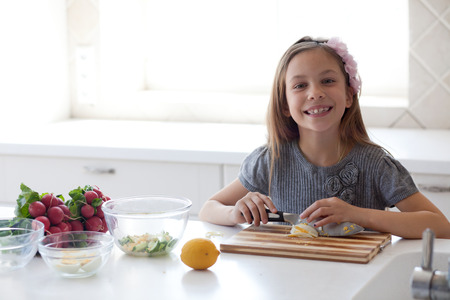 7 - 8 years old girl cooking in the white modern kitchen Stock Photo - 27342729