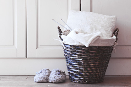 Wicker basket with warm blanket and knitting in it and soft slippers near it Stock Photo