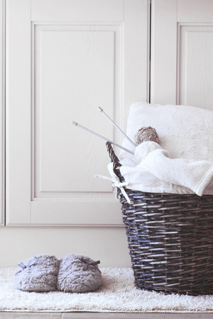 Wicker basket with warm blanket and knitting in it and soft slippers near it photo