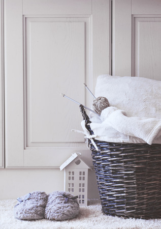 slipper: Wicker basket with warm blanket and knitting in it and soft slippers near it Stock Photo