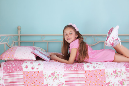 7 years old: Portrait of 7 years old school girl reading a book on pink bed in her nursery at home