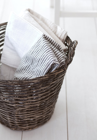storage bin: Wicker clothes basket with cotton linen in it