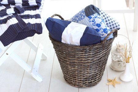 Wicker clothes basket with patchwork quilt and a pillow inside photo