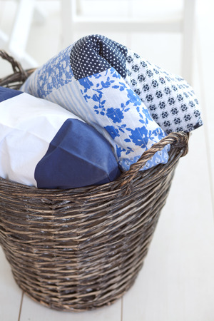 scandinavian: Wicker clothes basket with patchwork quilt and a pillow inside Stock Photo