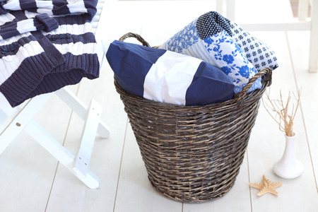 Wicker clothes basket with patchwork quilt and a pillow inside Stock Photo