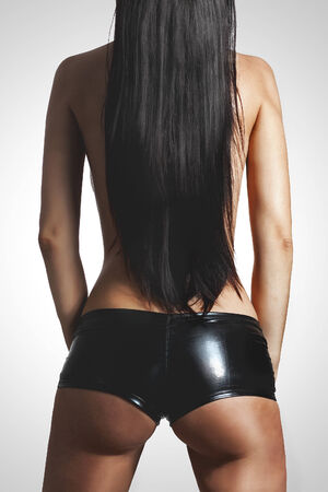 Beautiful brunette woman posing in black leather shorts studio shot photo