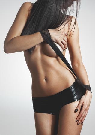 niña desnuda: Mujer hermosa morena posando en tiro negro pantalones cortos de cuero estudio