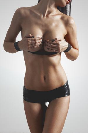 Beautiful brunette woman posing in black leather shorts studio shot photo