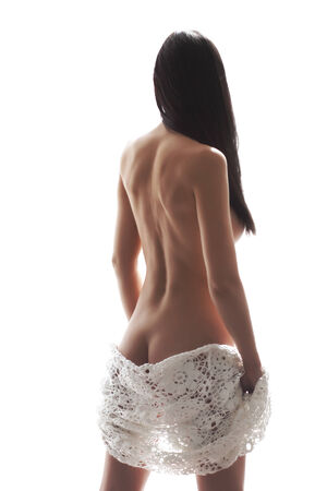 Portrait of a woman in lace underwear standing back in soft lighting isolated on white background photo