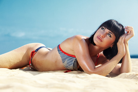 Portrait of beautiful young woman with fine figure resting at beach in summer looking up photo