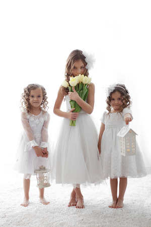 Beautiful little children wearing flower girl dresses posing with the bouquet of spring tulips Stock Photo - 27580117
