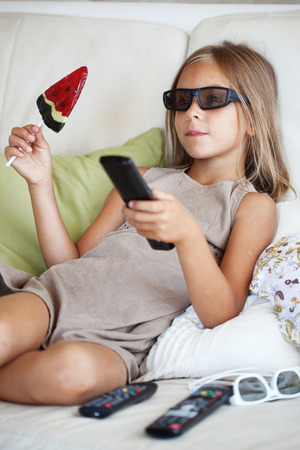 7 years old child watching tv sitting on sofa at home photo
