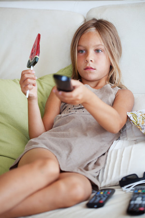 7 years old child watching tv sitting on sofa at home Stock Photo - 27580136