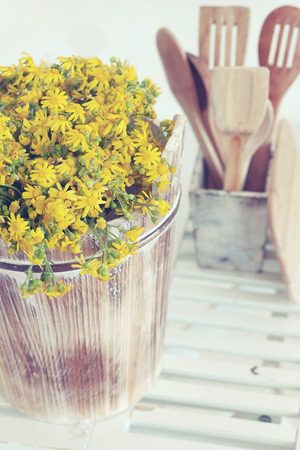 simple meal: Rustic photo of bunch of simple flowers in a old bucket on white wooden floor